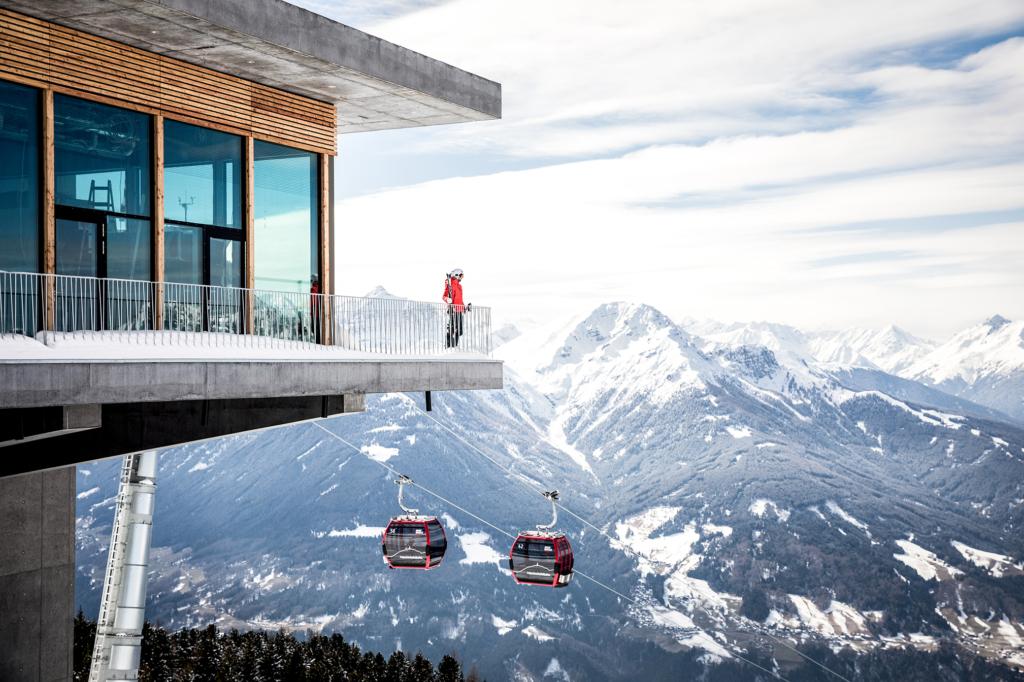 Person steht bei Patscherkofelbahn mit Bergen und Gondeln im Hintergrund